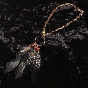 Feather, wood, and gold tone necklace